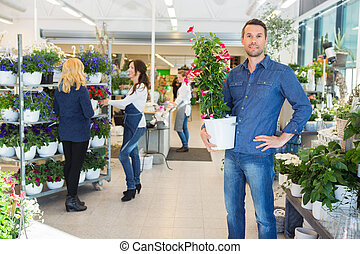 Confident Man Holding Flower Plant In Shop