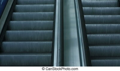 Confident man in black suit going up on the escalator
