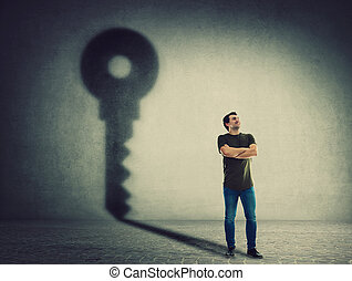 Confident man, keeps arms crossed, casting a key shadow on the wall. Ambition and business success concept