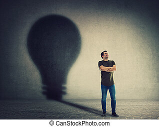 Confident man, keeps arms crossed, casting a lightbulb shape shadow on the wall. Ambition and business idea concept