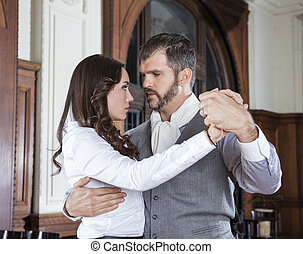 Confident Man Performing Tango With Woman In Restaurant