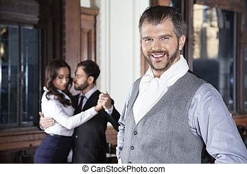 Confident Man Smiling While Dancers Performing Tango In Restaura