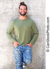 Confident man smiling with hands in pockets