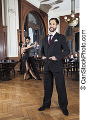 Confident Man Standing While Dancers Performing Tango