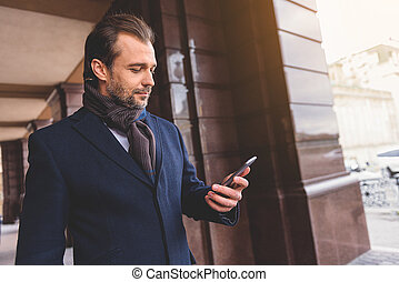 Confident man using mobile phone