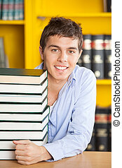 Confident Man With Piled Books Smiling In College Library
