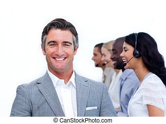 Confident manager and his team working in a call center