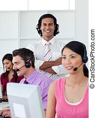 Confident manager checking his employee\'s work in a call center
