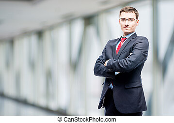 Confident manager in suit posing against in office