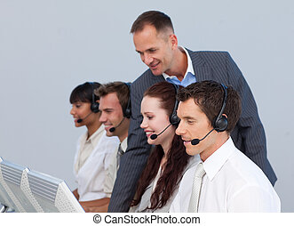 Confident manager with his team in a call center