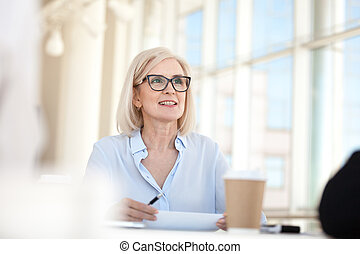 Confident mature business woman leader coach speaking at meeting