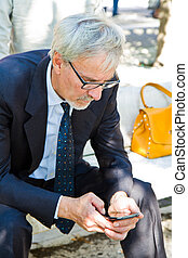 Confident mature businessman holding mobile phone and looking at it sitting outdoor