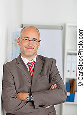 Confident Mature Businessman Leaning On Wall