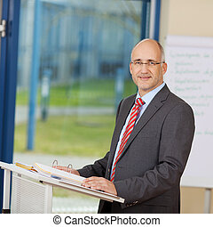 Confident Mature Businessman Standing At Podium