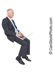 Confident mature businessman working on his laptop