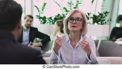 Confident mature senior businesswoman lawyer consulting client about contract, serious middle aged hr manager mentor explaining deal benefits interview applicant teaching employee at business meeting
