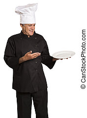Confident mature chef in black uniform holding empty plate.