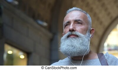 Confident mature guy listening to music while walking -...