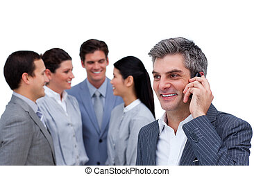 Confident mature manager on phone standig in front of his team