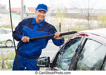 Confident Mature Serviceman Washing Car At Garage