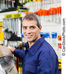 Confident Mature Worker Smiling In Hardware Shop