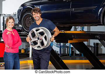 Confident Mechanic Holding Hubcap With Customer