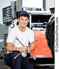 Confident Mechanic Holding Rim Wrench At Garage