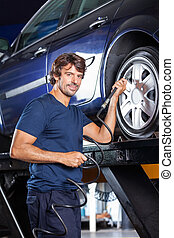 Confident Mechanic Refilling Air Into Car Tire At Garage