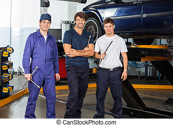 Confident Mechanics Holding Worktools At Garage