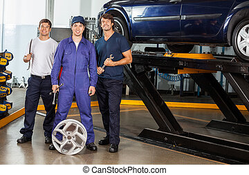 Confident Mechanics Holding Wrenches At Garage