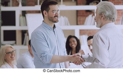 Confident middle aged company owner praising young smiling successful male manager with professional achievement, while excited multiracial coworkers clapping hands at business meeting in office.