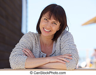 Confident middle aged woman smiling outside