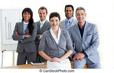Confident multi-ethnic business people around a conference table smiling at the camera