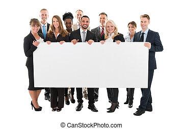 Confident Multi ethnic Business Team Holding Blank Billboard