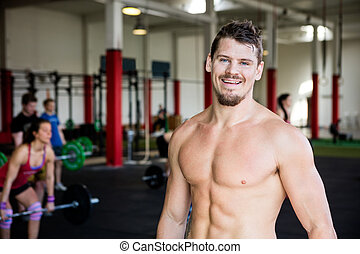 Confident Muscular Man Standing In Gym - Portrait of happy...