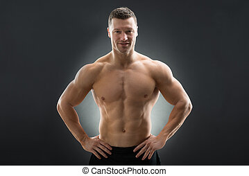 Confident Muscular Man Standing With Hands On Hip