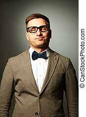 Confident nerd in eyeglasses and bow tie against grey...