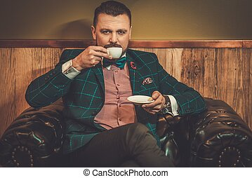 Confident old-fashioned man sitting in comfortable leather chair with cup of coffee in wooden interior at barber shop.