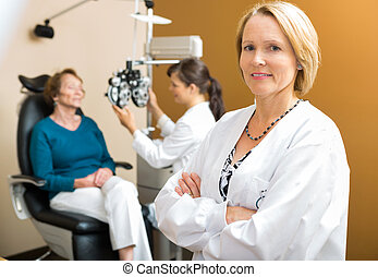 Confident Ophthalmologist With Colleague Examining Patient