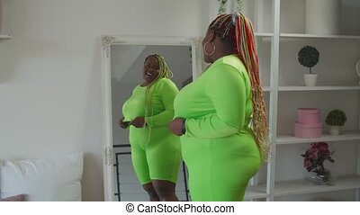 Confident overweight black woman looking at mirror - Smiling...