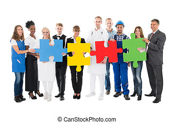 Confident People With Various Occupations Holding Jigsaw Pieces