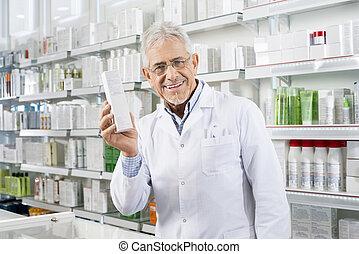 Confident Pharmacist Holding Medicine Box In Pharmacy