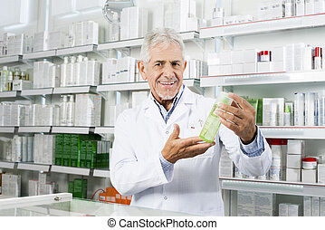 Confident Pharmacist Smiling While Holding Product In Pharmacy