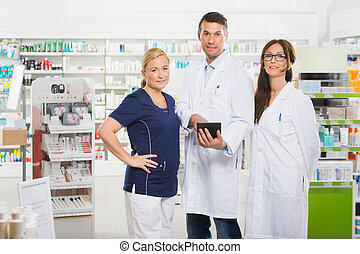 Confident Pharmacists With Digital Tablet Standing In...