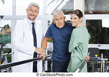 Confident Physiotherapists With Senior Patient In Fitness Studio