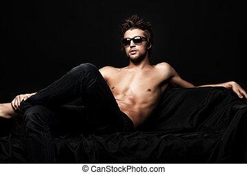 confident - Sexy shirtless man sitting on a sofa. Black...
