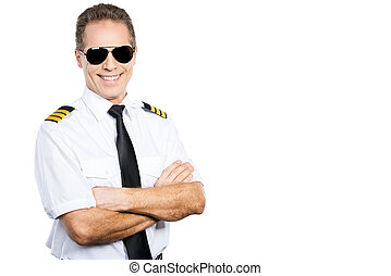 Confident pilot. Confident male pilot in uniform keeping arms crossed and smiling while standing against white background
