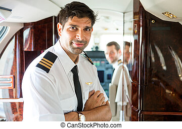Confident Pilot In Private Jet - Portrait of confident pilot...