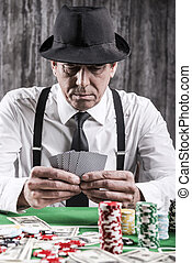 Confident poker player. Close-up of serious senior man in shirt and suspenders sitting at the poker table and holding cards with money and gambling chips laying all around him