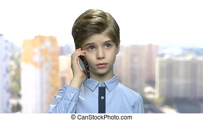 Confident preteen boy talking on cell phone. Smart caucasian...